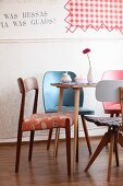 Various retro chairs around Gerbera, meringue and sugar bowl on table