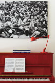 Sheet music and red lamp on red piano below large black and white photograph