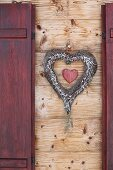 Heart-shaped wreath between window shutters on wooden façade