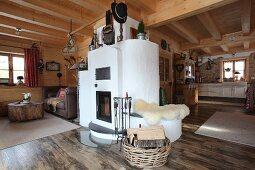 Masonry wood-burning stove in open-plan interior of wooden cabin
