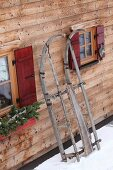 Rustic wooden sledge leaning against façade of wooden cabin
