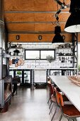 Open kitchen in industrial style, with concrete floor, subway tiles and wood-clad ceiling