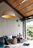Woman and child on sofa in high living room with trapezoidal sheet cladding next to patio door in industrial style