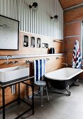 Vintage bathtub and vanity with countertop basin in the bathroom with trapezoidal sheet cladding and with wooden cladding