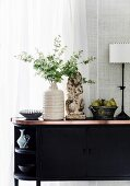 Black sideboard with decorative objects in front of a window