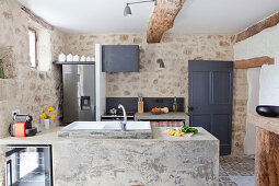 Exposed stone walls, beams and masonry counter in rustic kitchen