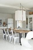 Langer Esstisch mit weißen Stühlen in der offenen Küche