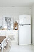 Retro-Kühlschrank in der Küche in Weiß mit Holzaccessoires