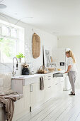 Frau steht an offener Schublade in heller Landhausküche