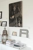 Bilder und Dekobuchstabe auf Wandleisten über dem Sideboard