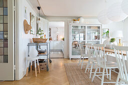 Windsor chairs at dining table in front of display case and open kitchen door