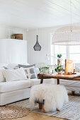 Sheepskin on stool in front of sofa in white living room
