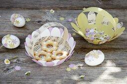 Pastellfarbene Körbe aus Papier und mit Papierblumen verzierte Ostereier
