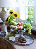Opulent fruit bowl on tray next to window
