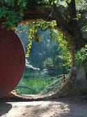 View through round doorway into lush garden