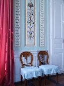 Two chairs against painted panelled wall