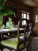 Antique chairs with green-upholstered seats at set table in farmhouse parlour