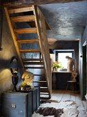 Holztruhe und Skulpturen im dunklen Flur mit offener Holztreppe