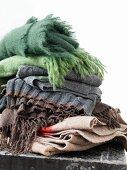 Verschiedene Wolldecken in Braun und Grün, gestapelt