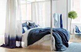 weiße Himmelbett mit Bettwäsche und Vorhang in Blau und Weiss in hellem Schlafzimmer