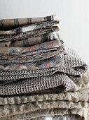 Bettwäsche und Decken in Sandfarben und in Grau, gestapelt