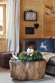 Advent wreath with four colourful candles on tree-stump coffee table in front of leather sofa