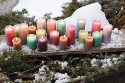 Colourful pillar candles on weathered wooden board amongst snow