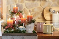 Arrangement of pillar candles, pine sprigs, pink pepper and air plants on floral crockery