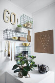 Wire baskets mounted on walls and used as shelves for kitchen utensils and ornaments