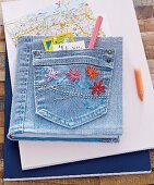 A notebook bound in denim with leftover wool flowers