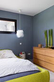 Double bed with green frame and houseplants on chest of drawers in bedroom with grey walls