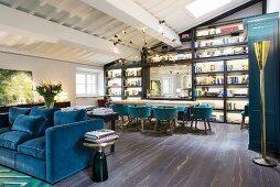 Offener Wohnraum mit blauem Polstersofa, im Hintergrund langer Tisch mit Schalenstühlen vor Regalwand