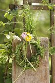 Wreath of grasses, decorated with cow parsley, red campion and buttercups on wooden fence