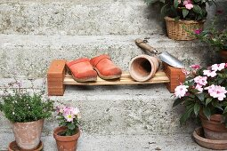 Garden clogs and plant pot on DIY cane shoe rack on stone steps