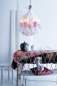 Embroidered silk chandelier above dining table with lidded jars on floral tablecloth