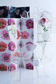 Floral fabric screen, white metal designer chair, coat stand and birdcage