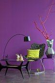 Glastisch mit Bogenlampe und bedruckter Sessel, Keramikvase mit Silberglasur auf Beistelltisch vor lila Wand