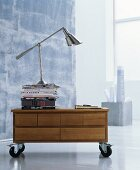 Stacked books and designer lamp on top of low sideboard on castors