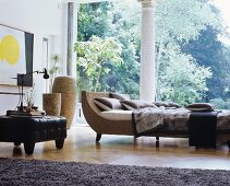 Cushions and blankets on couch next to black ottoman in front of panoramic window