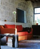 Orange sofa, side table and single allium flower in vase in front of rustic stone wall