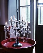 Candlelit candelabra on red tray in front of open French window