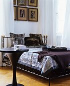 Fur cushions and fur blanket on black bed next to black table