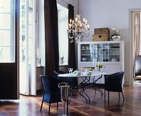 Black wicker chairs, chandelier and French windows in elegant dining area