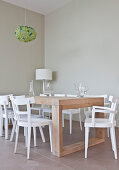 weiße Stühle um einen modernen Holztisch im schlichten Esszimmer