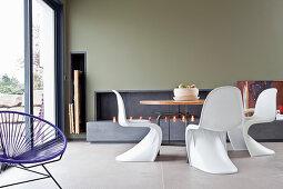 Designerstühle um einen runden Tisch vor dem bodentiefen Fenster