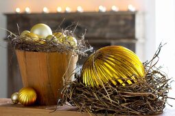 Christmas arrangement of gold baubles in pot and dried wreaths