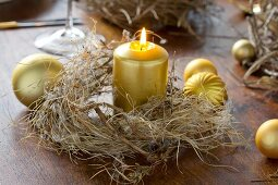 Gold candle in dried wreath on wooden table decorated with Christmas baubles