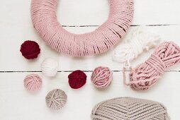 Balls of wool and wreath wrapped in pink yarn on white surface