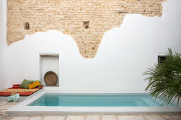 Partially rendered stone wall behind swimming pool