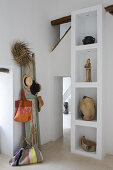 Old shutter used as coat rack next to souvenirs on white shelves